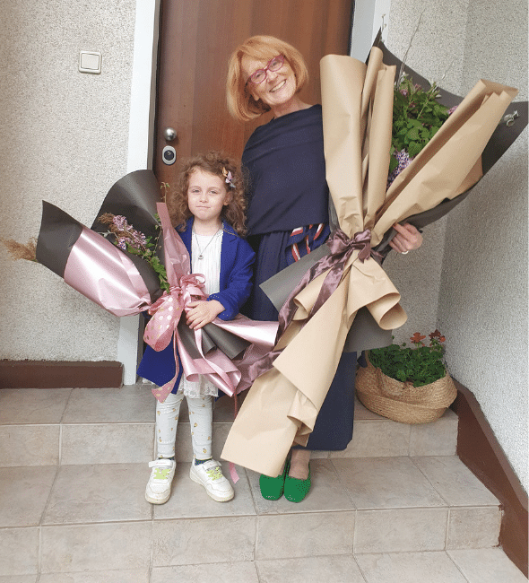 Grandma and granddaughter with big flower bouquets