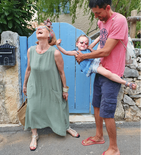 Woman in a long dress with a toddler girl and her father