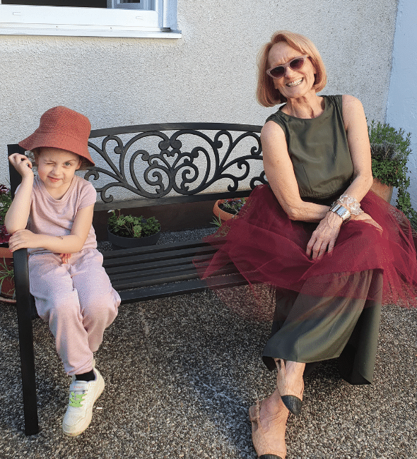 Grandma and grandaughter on a bench sitting